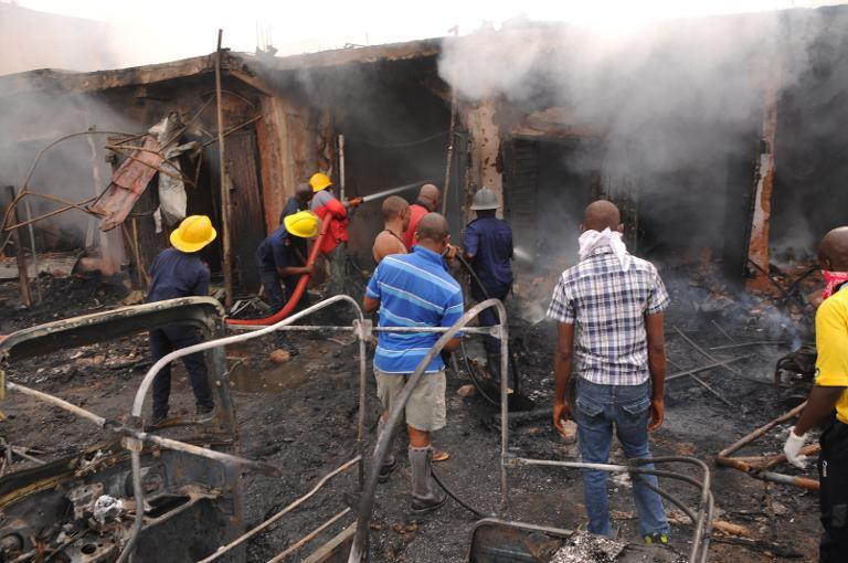 Firefighters extinguish a fire at the scene of a bomb blast at Terminus market in the central city of Jos on May 20, 2014