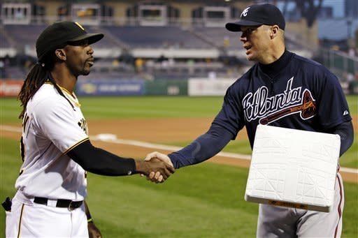 Atlanta Braves' Chipper Jones, right, receives a commemorative base from Pittsburgh Pirates' Andrew McCutchen during ceremony honoring his career before a baseball game in Pittsburgh, Monday, Oct. 1, 2012. (AP Photo/Gene J. Puskar)