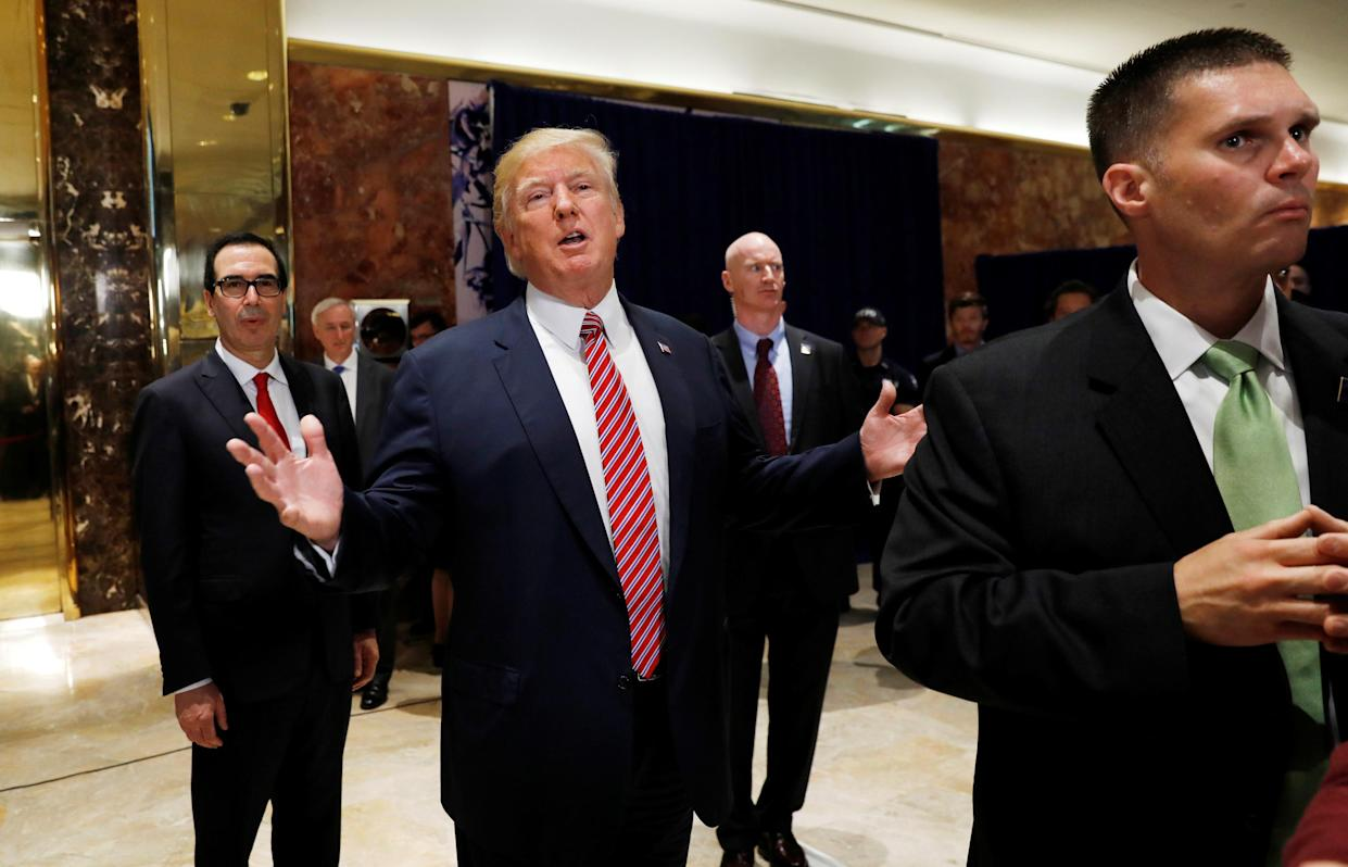 """At New York's Trump Tower, President Trump stops to respond to more questions about his responses to the violence, injuries and deaths at the """"Unite the Right"""" rally in Charlottesville. He is flanked by Treasury Secretary Steven Mnuchin, left,and U.S. Secret Service agents, right,after speaking to the media, Aug. 15, 2017. (Photo: Kevin Lamarque/Reuters)"""