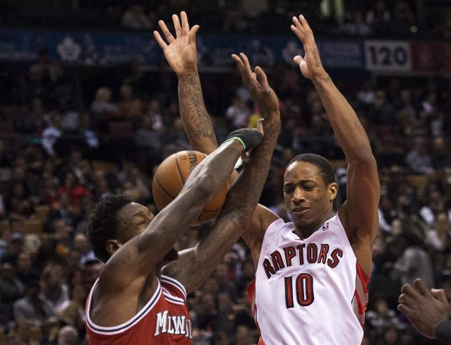 Toronto Raptors forward DeMar DeRozan (10) gets the ball stripped by Milwaukee Bucks forward Larry Sanders, left, during first half NBA basketball game in Toronto, Monday, Jan. 13, 2014. (AP Photo/The Canadian Press, Nathan Denette)