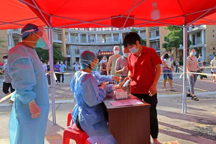 FILE PHOTO: Residents register to take nucleic acid tests at a testing site in Quanzhou, Fujian