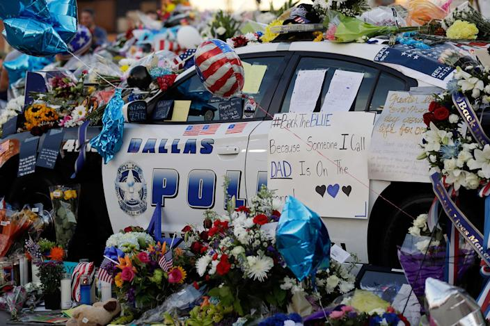 <p>JUL. 9, 2016 — Notes, flowers and other items decorate a squad car at a make-shift memorial in front of the Dallas police department in Dallas. Five police officers are dead and several injured following a shooting in downtown Dallas. (Eric Gay/AP) </p>