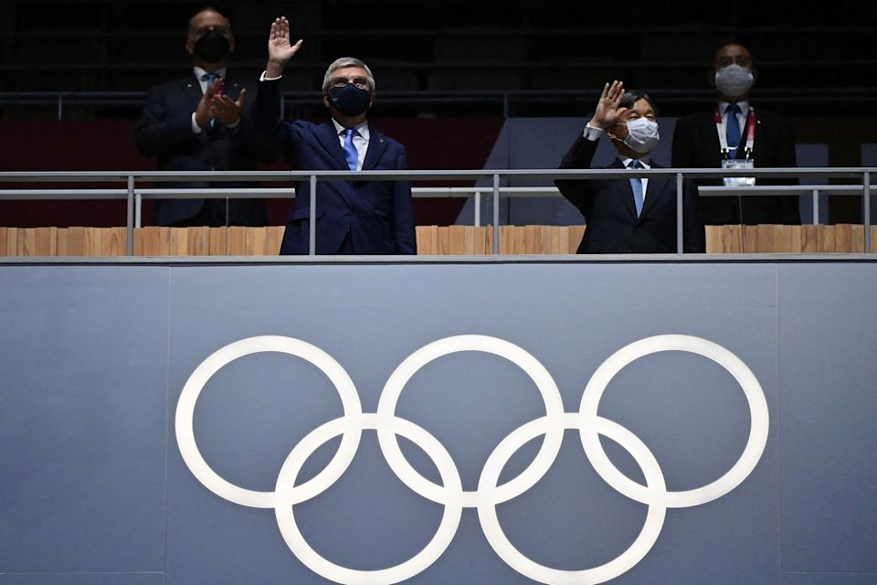 <p>TOPSHOT - President of the International Olympic Committee (IOC) Thomas Bach (L) and Japan's Emperor Naruhito wave during the opening ceremony of the Tokyo 2020 Olympic Games, at the Olympic Stadium, in Tokyo, on July 23, 2021. (Photo by Andrej ISAKOVIC / AFP) (Photo by ANDREJ ISAKOVIC/AFP via Getty Images)</p>