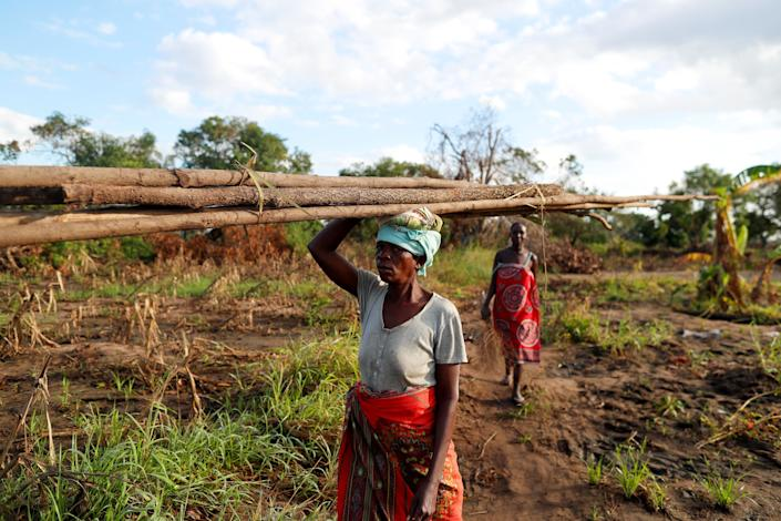 "Maria Jofresse, 25, walks behind her mother-in-law Teresa Miquitaio, 49, as she carries wood to build a makeshift shelter in the aftermath of Cyclone Idai, outside the village of Cheia, which means ""Flood"" in Portuguese, near Beira, Mozambique April 2, 2019. Maria Jofresse lost her two children to the storm. In the midst of the floods, she dug their small graves but can't find them anymore. ""People suffered indeed but no one suffered as I did because I lost the most precious things I had - my kids,"" she said. (Photo: Zohra Bensemra/Reuters)"
