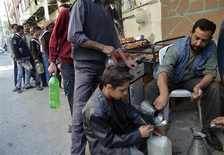 Civilians carry bottles as they queue to buy petrol in eastern al-Ghouta, near Damascus, October 22, 2013. REUTERS/Msallam Abd Albaset