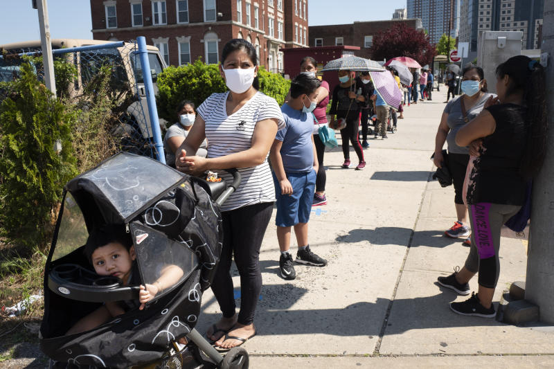 People wait in line to pick up bags of food and diapers at the Fuller Center for Housing in New Rochelle, N.Y., Tuesday, June 9, 2020, during the coronavirus pandemic. (AP Photo/Mark Lennihan)