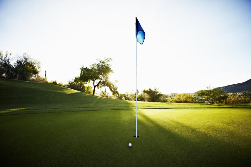 Golf ball next to flag on putting green on golf course at sunrise