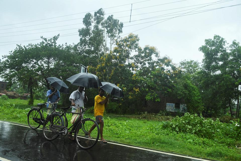 Villagers walk along a road under the rain ahead of the expected landfall of cyclone Amphan in Midnapore, West Bengal, on May 20, 2020. (Photo by DIBYANGSHU SARKAR/AFP via Getty Images)