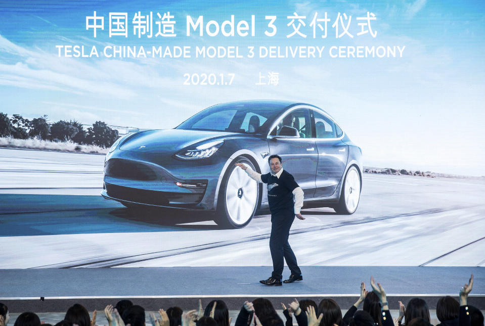 In this photo released by China's Xinhua News Agency, Tesla CEO Elon Musk reacts at a delivery ceremony for the first Tesla Model 3 cars made at Tesla's Shanghai factory in Shanghai, Tuesday, Jan. 7, 2020. Tesla's Shanghai factory delivered its first cars to customers Monday, and chief executive Elon Musk said the electric automaker plans to set up a design center in China to create a model for worldwide sales. (Ding Ting/Xinhua via AP)