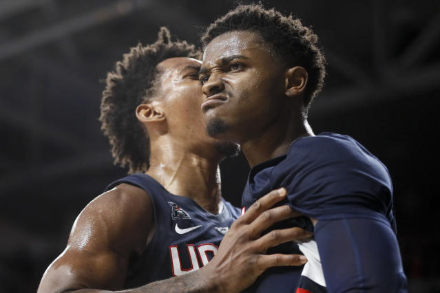 Connecticut's Alterique Gilbert, right, reacts after scoring and sending an NCAA college basketball game against Cincinnati into overtime in the second half Saturday, Jan. 12, 2019, in Cincinnati. (AP Photo/John Minchillo)