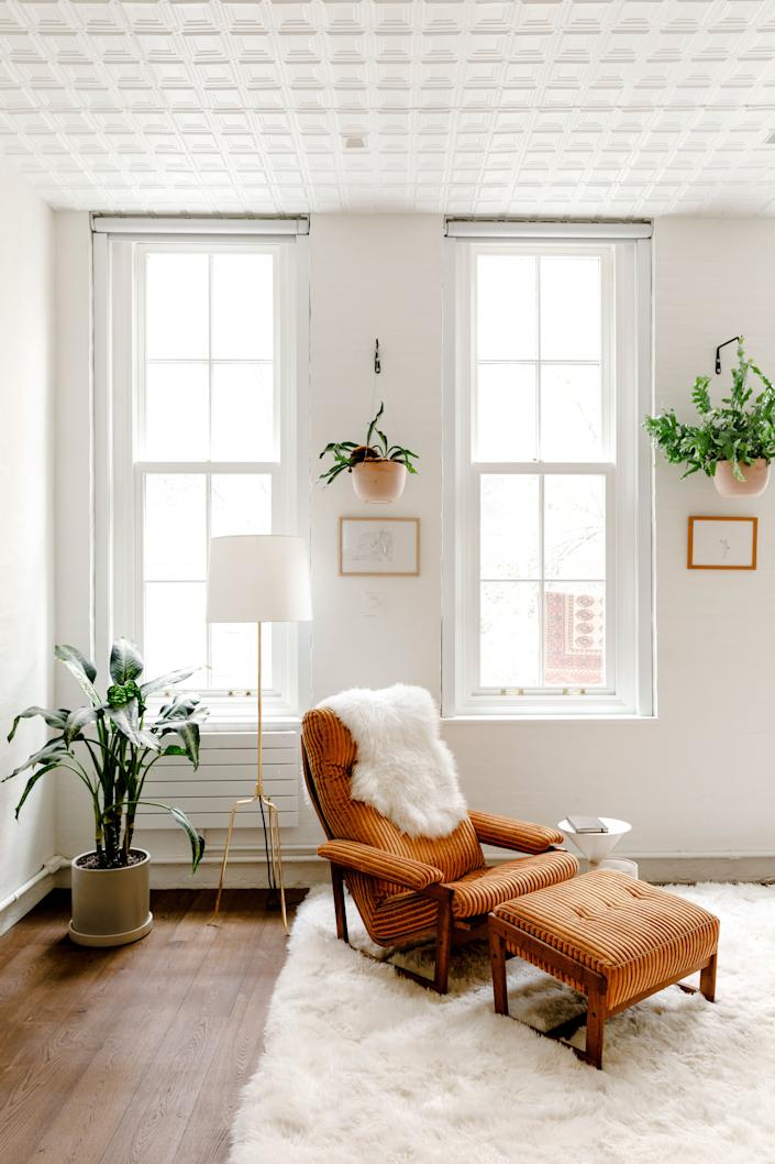 """Harbour's living room is flooded with light due to the oversized windows and 11-foot-high ceilings. One especially cozy corner features this vintage walnut chair from Chairish that O'Donnell reupholstered in """"Coomba"""" fabric from Missoni Home."""