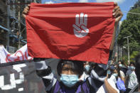 An anti-coup protester holds a slogan bearing the three-finger salute during a demonstration in Yangon, Myanmar on Tuesday May 11, 2021. The military takeover of Myanmar early in the morning of Feb. 1 reversed the country's slow climb toward democracy after five decades of army rule. But Myanmar's citizens were not shy about demanding their democracy be restored. (AP Photo)