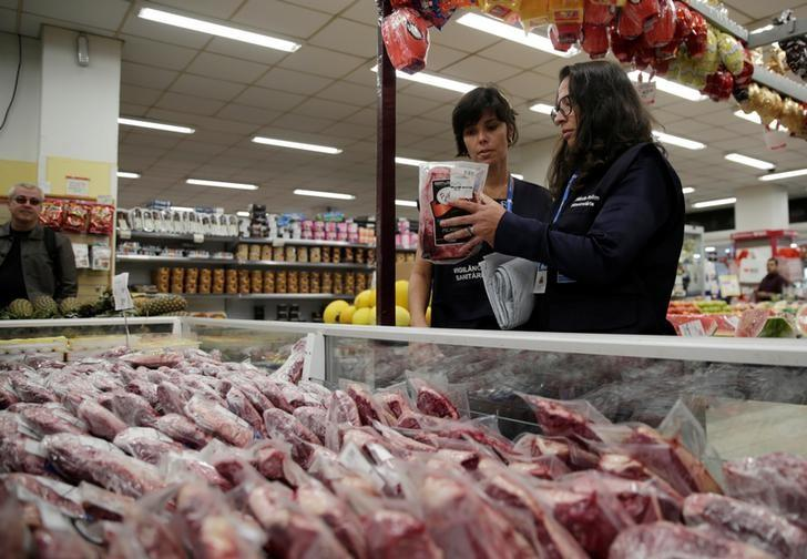 Members of the Public Health Surveillance Agency collect meats to analyse in their laboratory, at a supermarket in Rio de Janeiro