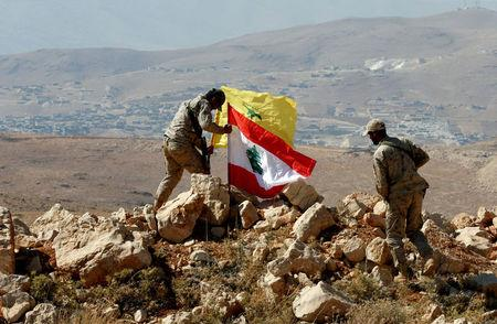 FILE PHOTO: Hezbollah fighters put Lebanese and Hezbollah flags at Juroud Arsal, Syria-Lebanon border