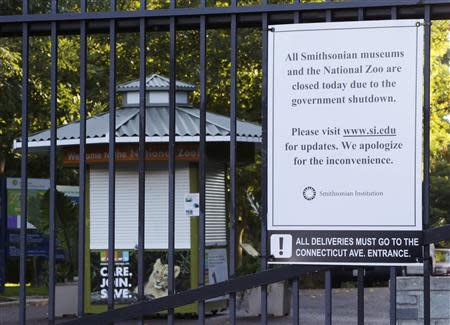 A sign (R) on a closed gate in front of the main welcome booth (L) notifies visitors that Smithsonian National Zoo is closed due to the government shutdown in Washington October 2, 2013. REUTERS/Gary Cameron