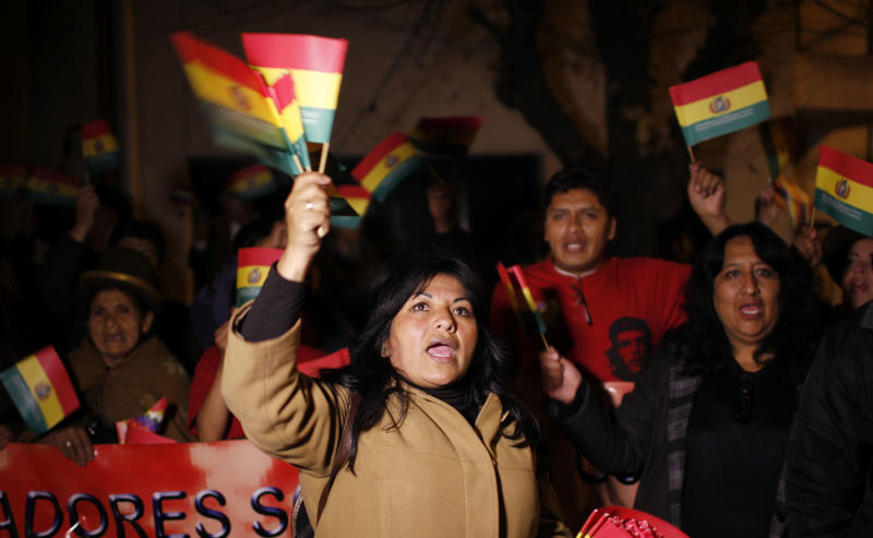 Supporters of Bolivia's President Evo Morales shout and wave Bolivian flags outside France's embassy as they protest in La Paz, Bolivia, Tuesday, July 2, 2013. Bolivia's Foreign Minister David Choquehuanca says the plane bringing President Evo Morales home from Russia was rerouted to Austria after France and Portugal refused to let it to cross their airspace because of suspicions that NSA leaker Edward Snowden was on board. Officials in both Austria and Bolivia said that Snowden was not on the plane. (AP Photo/Juan Karita)