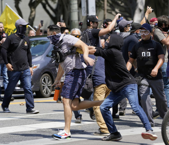 Anti-vaccination demonstrators and counter-protesters clash during an anti-vaccination protest in front of the City Hall in Los Angeles on Saturday, Aug. 14, 2021. A man was stabbed and a reporter was attacked Saturday at a protest against vaccine mandates on the south lawn of Los Angeles' City Hall after a fight broke out between the protesters and counter-protesters, the Los Angeles Police Department and local media said. (AP Photo/Damian Dovarganes)