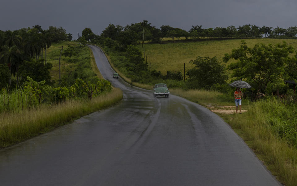 A woman walks on the shoulder of a road using an umbrella as protection against rains brought on by Hurricane Ida, in Guanimar, Artemisa province, Cuba, Saturday, Aug. 28, 2021. (AP Photo/Ramon Espinosa)