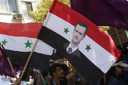 Supporters of Syria's President Bashar al-Assad wave a Syrian national flag depicting Assad's portrait during a rally in Damascus