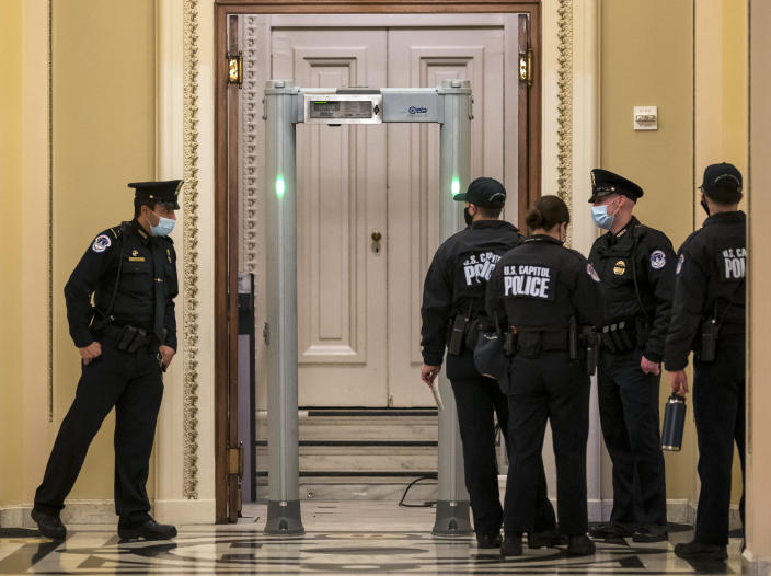 U.S. Capitol Police survey the corridor around the House of Representatives chamber after enhanced security protocols were enacted, including metal detectors for lawmakers, after a mob loyal to President Donald Trump stormed the Capitol, in Washington, Tuesday, Jan. 12, 2021. (AP Photo/J. Scott Applewhite)