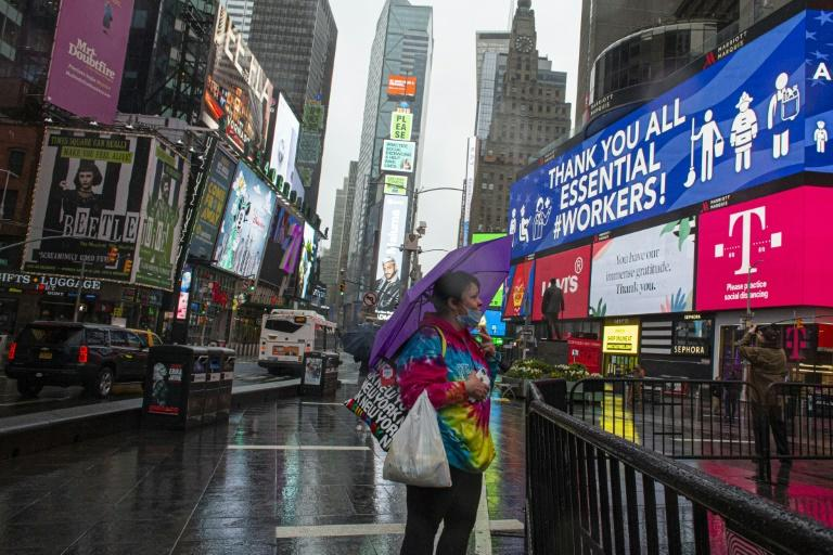 A woman covers herself from the rain as she visits Times Square amid the coronavirus pandemic on April 26, 2020 in New York City