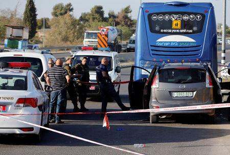 Israeli policeman inspects the scene of a Palestinian car ramming attack at the Gush Etzion Junction, south of the West Bank city of Bethlehem