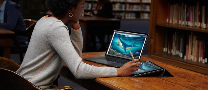 Woman using MacBook and iPad Pro at a desk in a library with bookshelves in the background