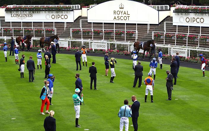 Jockeys and trainers are socially distanced in the paddock during day one of Royal Ascot at Ascot Racecourse. - BHA Pool