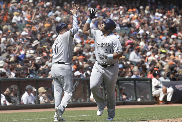 Milwaukee Brewers' Jesus Aguilar, right, celebrates with third base coach Ed Sedar after hitting a solo home run against the San Francisco Giants during the sixth inning of a baseball game in San Francisco, Sunday, June 16, 2019. (AP Photo/Jeff Chiu)