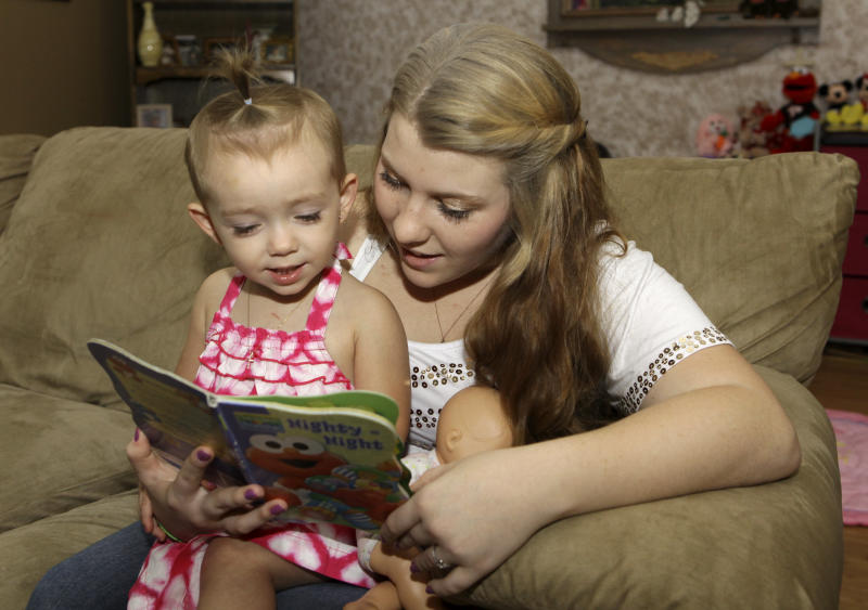 In this Monday, Sept. 10, 2012 photo, Kali Gonzalez reads to her daughter Kiah, 2, at their home in St. Augustine, Fla. A new report by the National Women's Law Center says offering pregnant teens extra support would ultimately save taxpayers money by helping them become financially independent and not dependent on welfare. (AP Photo/John Raoux)