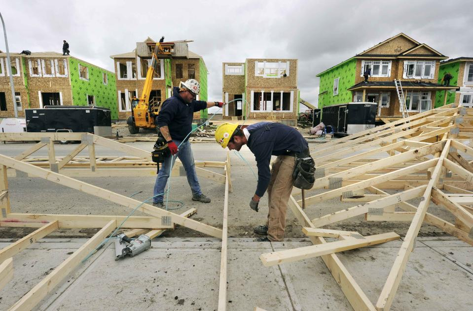 Construction workers work on building new homes in Calgary, Alberta, in this file photo taken May 31, 2010. A year ago, one of the hottest parts of Canada's red-hot housing market was Alberta's oil capital of Calgary, where cash-rich consumers fought for the fanciest home on the block. Now, a plunge in crude prices is pulling the housing market with it. REUTERS/Todd Korol/Files (CANADA - Tags: BUSINESS INDUSTRIAL REAL ESTATE)
