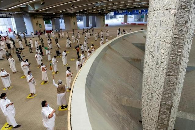 Muslim pilgrims throw stones at a large pillar symbolising the devil, spaced apart on marked spots to maintain social distancing, in the last major ritual of this year's scaled back hajj