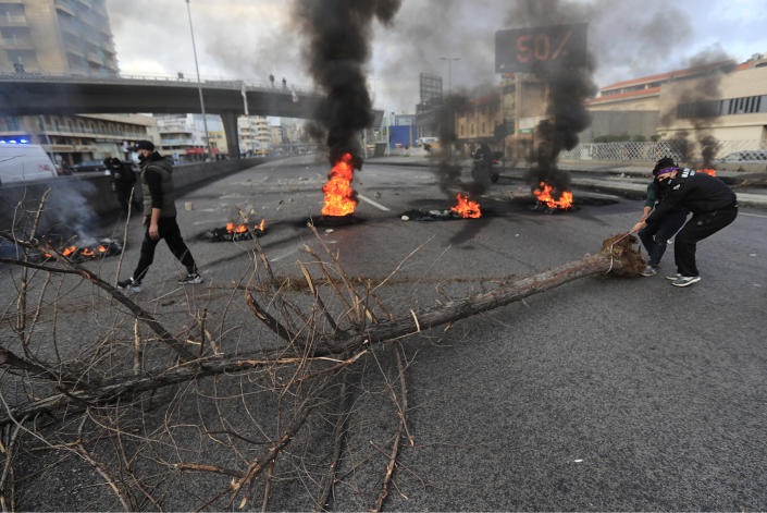 Protesters move a tree in front of burned tires to block a main highway, during a protest in the town of Jal el-Dib, north of Beirut, Lebanon, Monday, March 8, 2021. The dayslong protests intensified Monday amid a crash in the local currency, increase of consumer goods prices and political bickering between rival groups that has delayed the formation of a new government. (AP Photo/Hussein Malla)