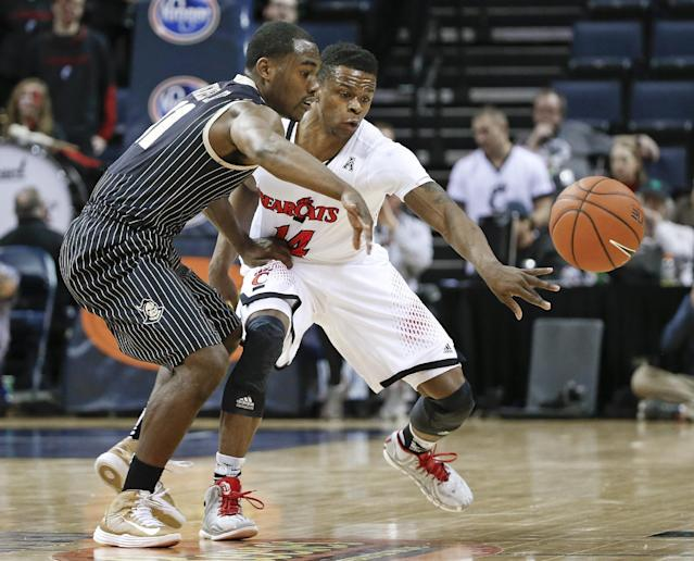 Cincinnati guard Ge'Lawn Guyn (14) knocks the ball away from Central Florida's Calvin Newell (11) during the first half of an NCAA college basketball game in the quarterfinals of the American Athletic Conference men's tournament Thursday, March 13, 2014, in Memphis, Tenn. (AP Photo/Mark Humphrey)
