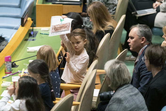 A young member of the Polish delegation shows off a drawing she made during the 30th anniversary of the adoption of the Convention on the Rights of the Child, Wednesday, Nov. 20, 2019, at United Nations headquarters. (AP Photo/Mary Altaffer)