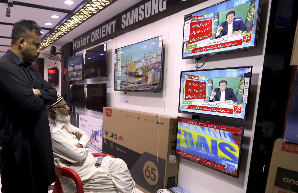 People watch a live address to the nation by Pakistan's Prime Minister Imran Khan, at a shop in Karachi, Pakistan, Thursday, March 4, 2021. Khan on Thursday announced he would seek a vote of confidence from the National Assembly this weekend to prove he still has the support of majority lawmakers in the house, despite the surprising and embarrassing defeat of his ruling party's key candidate in Senate's elections. (AP Photo/Fareed Khan)
