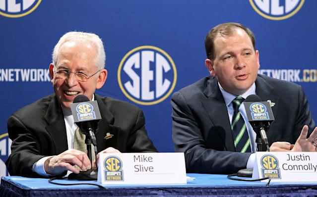 Southeastern Conference Commissioner Mike Slive, left, laughs as he listens to SEC Network President Justin Connolly, right, during a press conference the day before the SEC Football Championship game at the Georgia Dome, Friday, Dec. 6, 2013, in Atlanta, Ga., (AP Photo/Atlanta Journal-Constitution, Jason Getz)