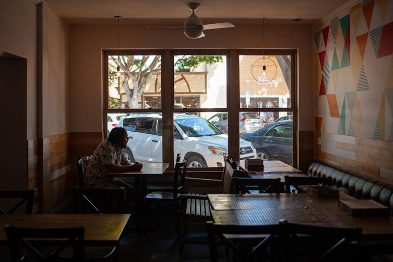Gabriel Gordon, owner of a popular barbecue restaurant in Seal Beach, Calif., sits inside his closed restaurant on July 7, 2020. (Horatio Baltz/The New York Times)