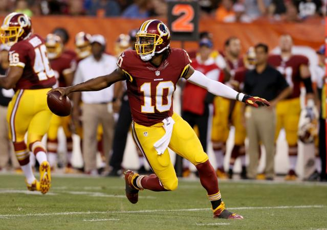 FILE - In this Thursday, Aug. 13, 2015 file photo, Washington Redskins quarterback Robert Griffin III (10) scrambles against the Cleveland Browns during an NFL preseason football game in Cleveland. Robert Griffin III, the 2012 Offensive Rookie of the Year whose subsequent seasons have been marred by injuries, will face the team that chose him second overall that year and made the playoffs behind him. While RG3 has, by all accounts, had a solid summer, there's no guarantee he will make the Ravens, who have Joe Flacco entrenched as the starter and first-round draftee Lamar Jackson as his understudy. (AP Photo/Ron Schwane, File)