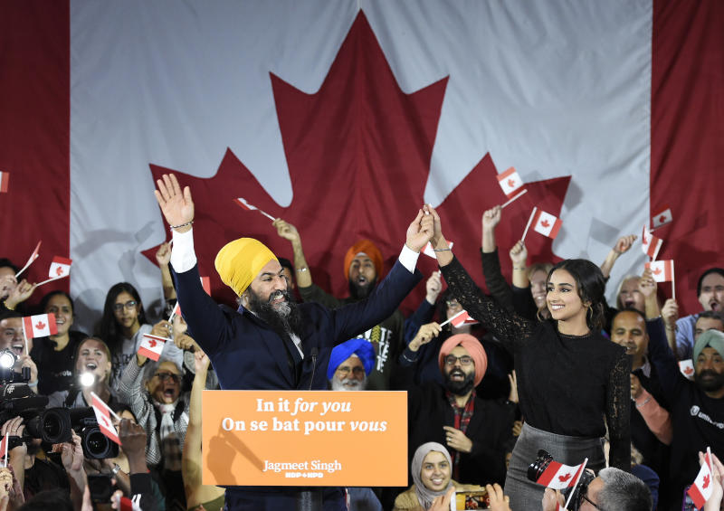 NDP leader Jagmeet Singh and his wife Gurkiran Kaur wave to supporters on stage at NDP election headquarters in Burnaby, British Columbia, on Monday, Oct. 21, 2019. (Nathan Denette/The Canadian Press via AP)