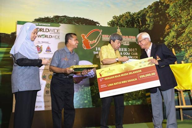For a worthy cause, Sultan Sharafuddin Idris Shah presents a mock cheque to Raja Arshad (right) as Datuk Nordin Sulaiman (second,left) and Datin Paduka Norazlina Zakaria look on. — Picture by Azneal Ishak