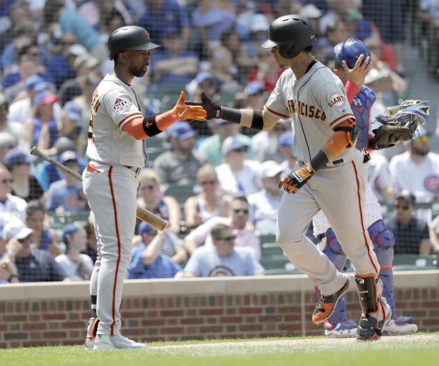 San Francisco Giants' Andrew McCutchen, left, greets Gorkys Hernandez at home plate after Hernandez's home run off Chicago Cubs starting pitcher Kyle Hendricks during the fourth inning of a baseball game Friday, May 25, 2018, in Chicago. (AP Photo/Charles Rex Arbogast)