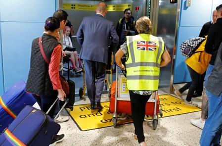 A British Government official assists passengers at Manchester Airport