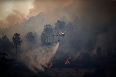 FILE PHOTO - A firefighting helicopter drops water to extinguish a forest fire in Vila Velha de Rodao