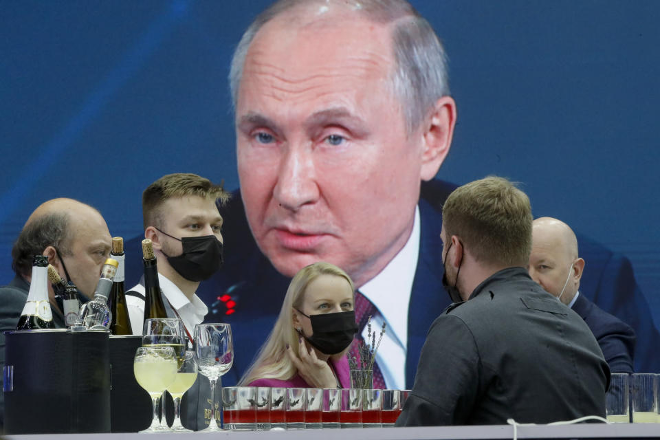 Journalists gather in the press center as they listen to Russian President Vladimir Putin speaking, at the St. Petersburg International Economic Forum in St. Petersburg, Russia, Friday, June 4, 2021. (AP Photo/Dmitri Lovetsky)