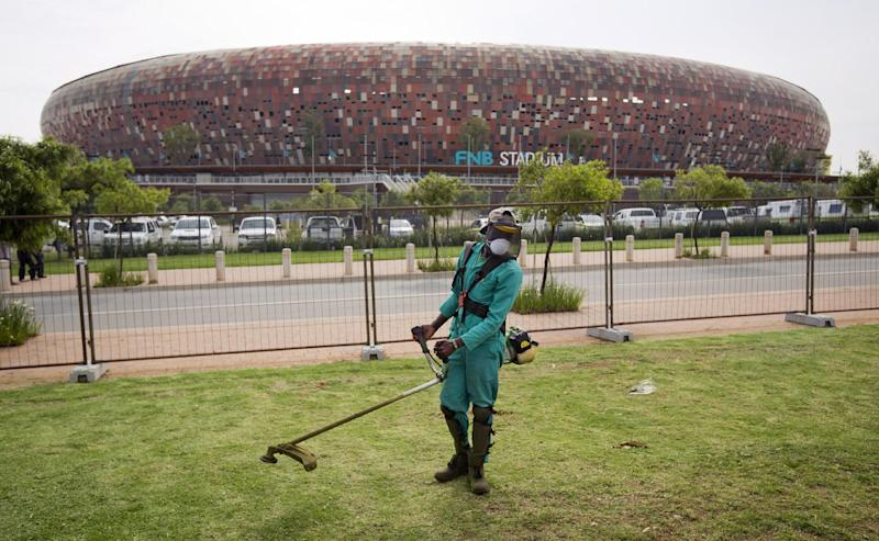 A worker trims the grass outside the FNB stadium where the memorial service for Nelson Mandela will take place on Tuesday, in Johannesburg, South Africa Monday, Dec. 9, 2013. Scores of heads of state and government and other foreign dignitaries, including royalty, are beginning to converge on South Africa as the final preparations for Tuesday's national memorial service for liberation struggle icon Nelson Mandela are put in place. (AP Photo/Ben Curtis)