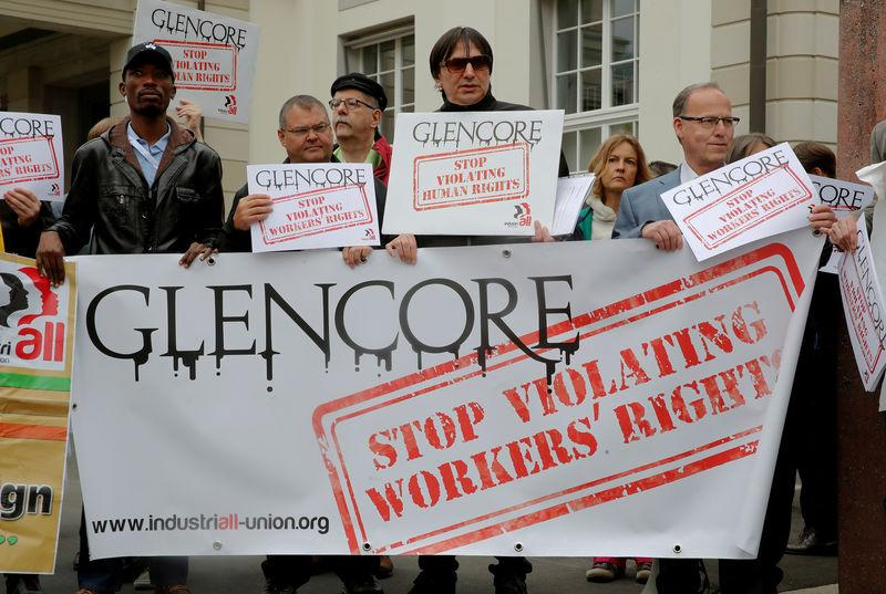 FILE PHOTO: Protesters display a banner and posters in front of the venue of commodities trader Glencore's annual shareholder meeting in Zug