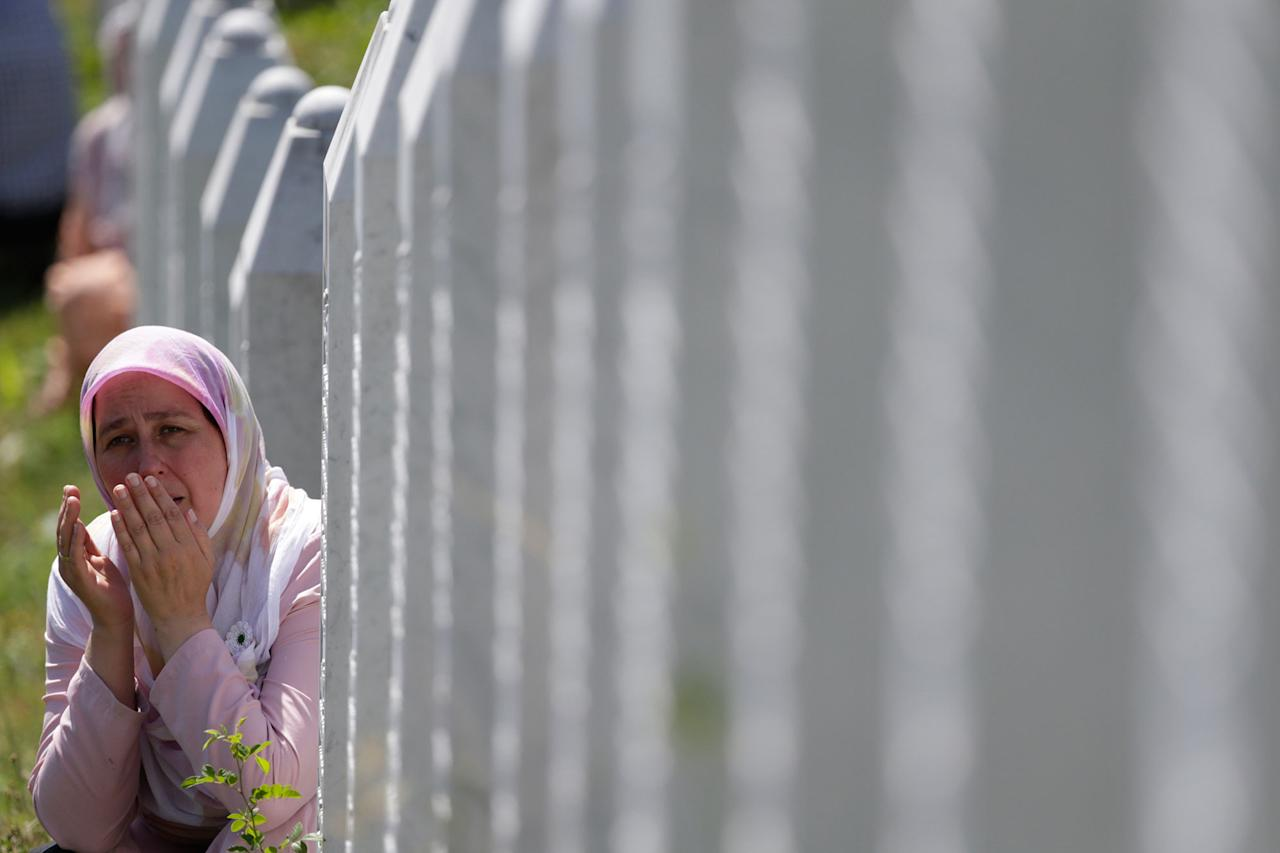 <p>A Bosnian Muslim woman prays among gravestones during a funeral ceremony for dozens of newly identified victims of the 1995 massacre, at the memorial centre of Potocari near Srebrenica, 150 kms north east of Sarajevo, Bosnia, Tuesday, July 11, 2017. (Photo: Amel Emric/AP) </p>
