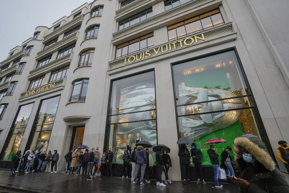 """People line up as they wait to get in the Louis Vuitton shop on the Champs Elysee avenue in Paris, Wednesday, May 19, 2021. Shops, cafe and restaurant terraces reopened Wednesday after a six-month coronavirus shutdown deprived residents of the essence of French life """" sipping coffee and wine with friends """". (AP Photo/Michel Euler)"""