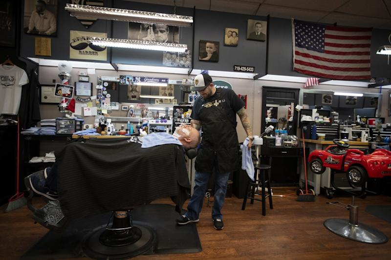 Cañon City Councilman Brandon Smith, right, owns a barbershop on Main Street.